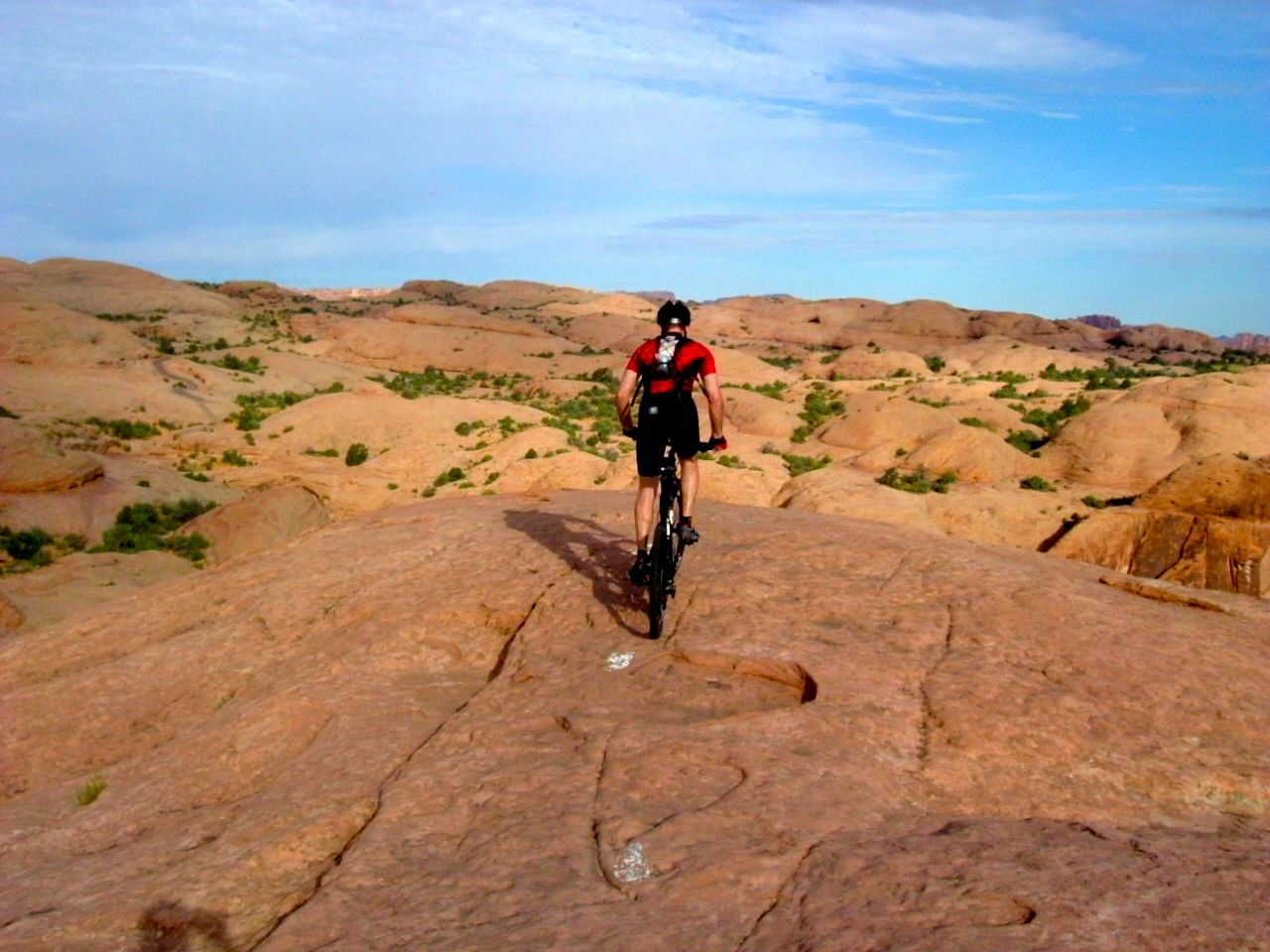 My husband riding Slick Rock into the abyss.