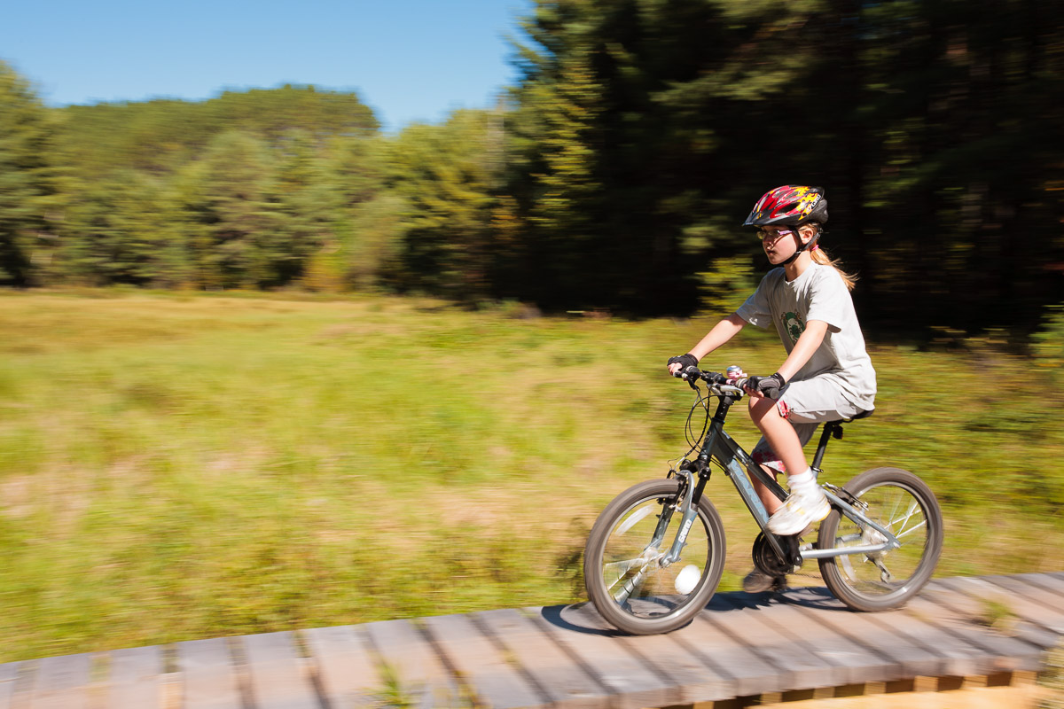 Emma rides a bridge across a swamp on the CAMBA trails