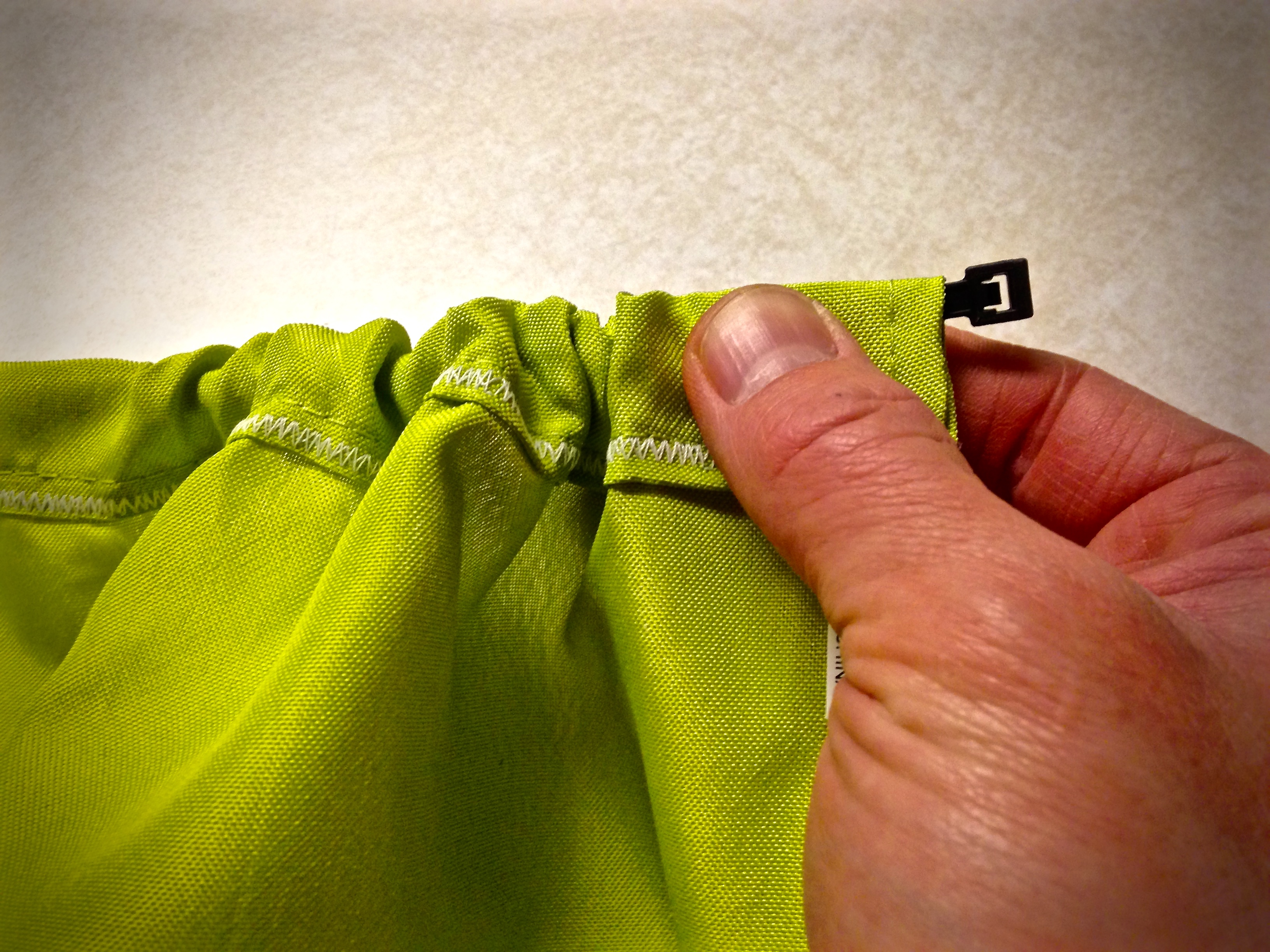 Hold ziptie at its neck and gather fabric until end of ziptie pops out on other side