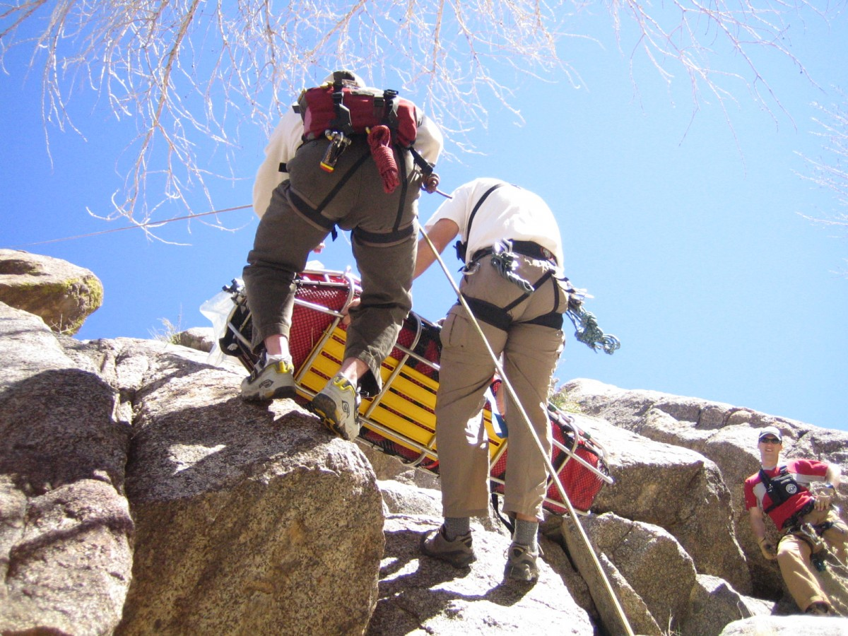 "Practicing bag-ventilating a ""patient"" while rappelling down a 100ft cliff near Albuquerque. Part of a month long wilderness medicine course I completed in 2004."