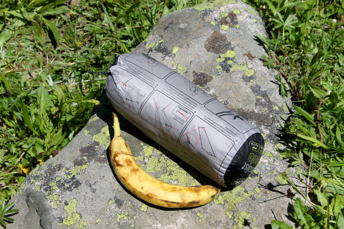 Tent rolled up in storage bag, complete with poles and stakes. Banana for scale.