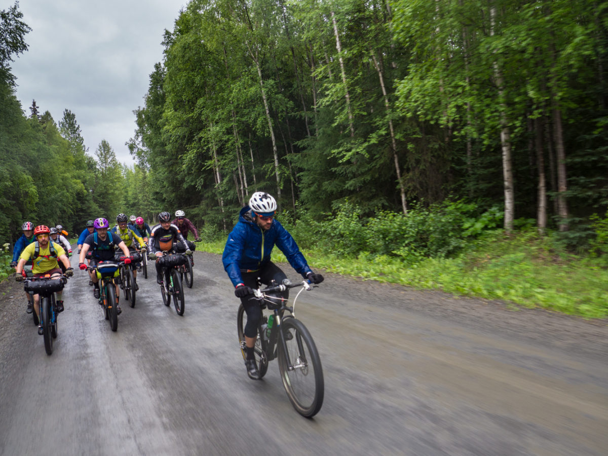 The lead pack of the 2016 edition of the Kenai 250, minutes after the start, soaked through, riding uphill, against a headwind. Welcome to the strange world of bikepacking races!
