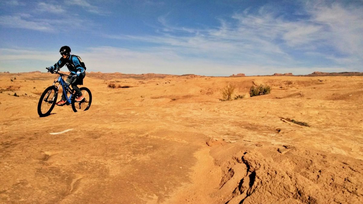The Slickrock trail in Moab is a great example of little monuments (i.e. punchy climbs). Work hard to get up each one as losing the momentum requires bike pushing and can be dangerous at times. Rider: Monica Nelson at the top after owning one of the climbs. Photo: Aaron Couch