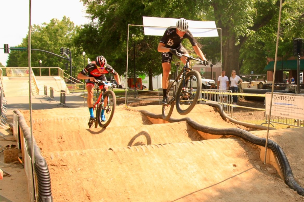 Two mountain bikers ride all out in a compeitition.